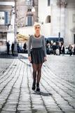 走在街道上的白肤金发的女孩在穿着裙子的城市 免版税库存图片