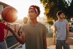 走在街道上的篮球人使用与球 免版税库存照片