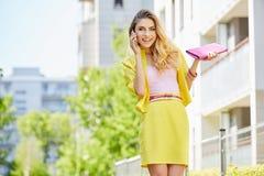 走在街道上的美丽的白肤金发的少妇 免版税库存照片
