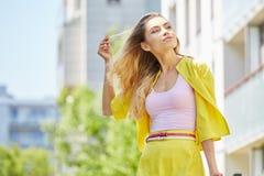 走在街道上的美丽的白肤金发的少妇 免版税图库摄影