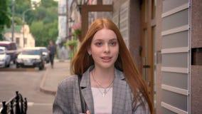 走在街道和微笑的年轻迷人的姜妇女,愉快,拿着在一肩膀的背包 影视素材