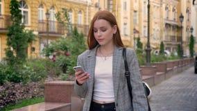 走在街道和看她的电话,黄色大厦背景的年轻美丽的姜妇女 股票录像