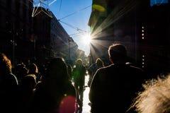 走在街道太阳火光城市人群的人们现出轮廓Sidewa 库存照片