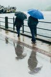 走在街道的两个人在一个雨天 库存照片