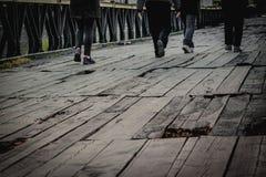 走在被毁坏的木brige的人们 库存照片