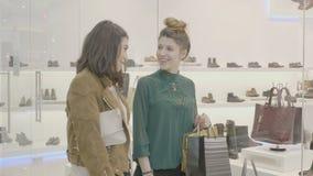 走在购物中心运载的购物袋和寻找一双短剑鞋的女性表兄弟匹配礼服- 股票录像