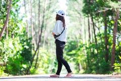 走在走道的亚洲女服便衣在绿色前面 免版税库存照片