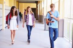 走在走廊的高中学生使用手机 免版税图库摄影