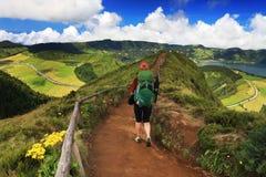 走在足迹的妇女导致绿色和蓝色湖,圣地米格尔海岛 库存照片