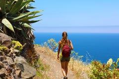 走在足迹的年轻徒步旅行者妇女俯视海在特内里费岛 库存图片