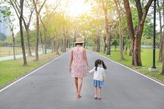 走在路和握手的母亲和她的女儿在室外自然庭院里 r 免版税库存图片