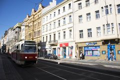走在路和有轨电车旁边的旅客人运行在Jindrisska路去亨利` s钟楼 库存图片