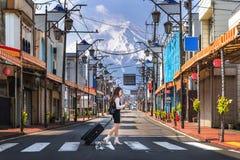 走在路的妇女在富士吉田市有富士山,日本背景  免版税图库摄影