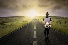 走在路的孤独的吉他弹奏者 免版税库存照片