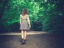 走在路的少妇在森林里 免版税库存图片