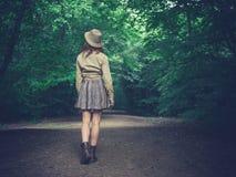 走在路的少妇在森林里 免版税库存照片