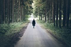 走在路的年轻白肤金发的白种人妇女通过黑暗的森林 图库摄影