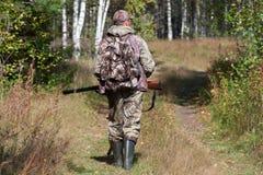 走在路的猎人在秋天森林里 库存照片
