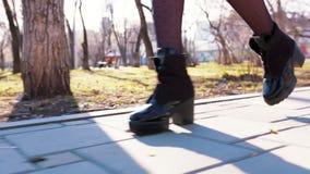 走在路的美女的腿和贴身衬衣特写镜头在高黑脚腕起动的在有树的公园在春天 股票录像