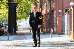 走在边路的盲人拿着棍子 免版税库存图片