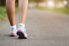 走在道路和光的妇女腿 库存照片