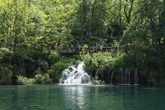 走在道路的人们在瀑布附近 库存图片