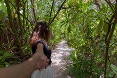 走在道路的年轻女人的跟我学概念围拢由绿色植被 免版税库存照片