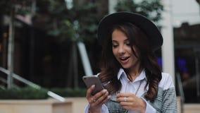 走在都市街道上的愉快的年轻女实业家使用智能手机 概念:新的事务,通信,银行家 影视素材