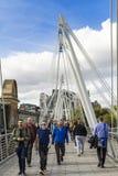 走在金黄周年纪念桥梁的人们在伦敦大英国 免版税库存照片
