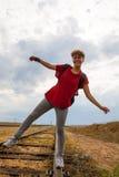 走在铁路的微笑的青少年的女孩 免版税库存图片