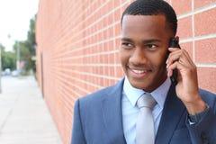 走在镇里和拜访手机的英俊的非裔美国人的现代商人 免版税图库摄影