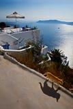 走在阳光下与圣托里尼海景的猫 库存图片