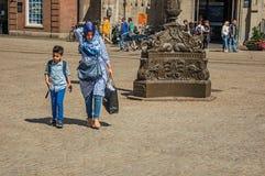 走在阿姆斯特丹的妇女佩带的hijab头巾和孩子摆正 免版税图库摄影