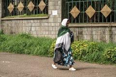 走在阿迪斯街道上的一名更老的埃赛俄比亚的妇女  免版税图库摄影