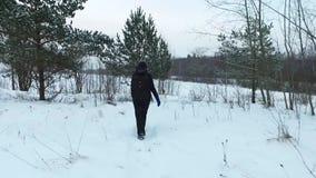 走在降雪的年轻女人的慢动作背面图 steadicam射击 股票视频