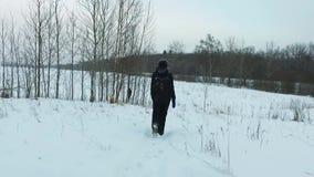走在降雪的年轻女人的慢动作背面图 steadicam射击 股票录像