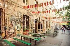 走在难看的东西街道咖啡馆和街道画艺术品附近的人们 免版税库存照片