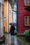 走在雨中通过狭窄的街道在卑尔根老镇 库存照片