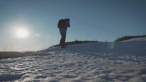走在雪山的背包徒步旅行者在冬天 有迁徙在山的背包的人 高涨魔术其它短小冬天木头 股票录像