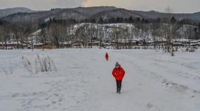 走在雪村庄的妇女在中国 免版税库存照片
