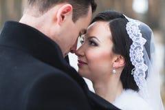 走在雪的一个冬天森林里的年轻夫妇新婚佳偶 免版税库存图片