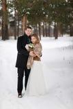 走在雪的一个冬天森林里的年轻夫妇新婚佳偶 库存图片