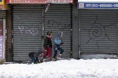 走在雪的人们在纽约布朗克斯县猛冲 免版税库存照片