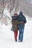 走在雪的男孩和女孩 免版税库存图片