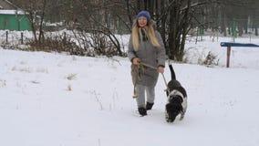 走在雪的美丽的快乐的女孩狗尖 股票视频