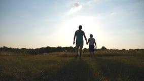 走在领域在日落和握手彼此的父亲和儿子剪影  花费时间的愉快的家庭 股票录像