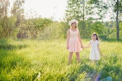 走在领域的妈妈和女儿在夏天晴天在日落 库存图片