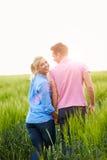 走在领域的浪漫夫妇握手 免版税库存照片