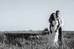 走在领域的年轻新婚佳偶夫妇在室外的阳光下 免版税图库摄影