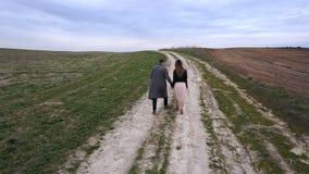 走在领域的年轻美好的夫妇 鸟瞰图、寄生虫飞行在人以后和妇女,他们停止和亲吻 股票录像